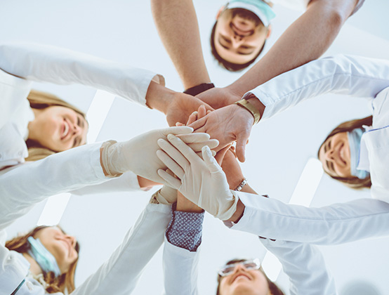 The team at Northstar Dental placing their hands together in a team huddle