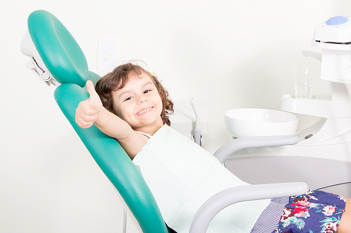 Smiling girl sitting in dental chair giving a thumbs up